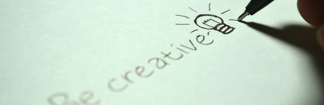 "White paper and a pen writing words ""Be creative""."