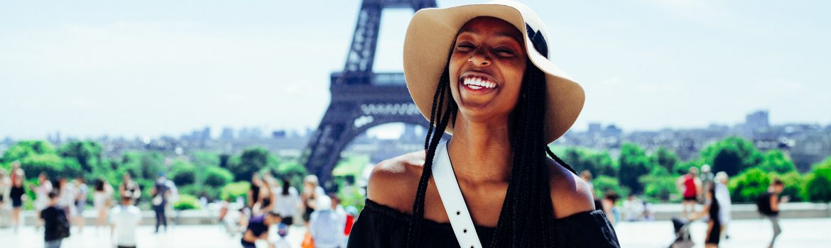 Eiffel tower in Paris and a girl smiling in a black dress.