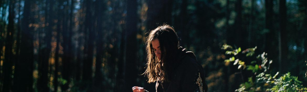 A girl in the forest sitting on stump and making some notes in her book.