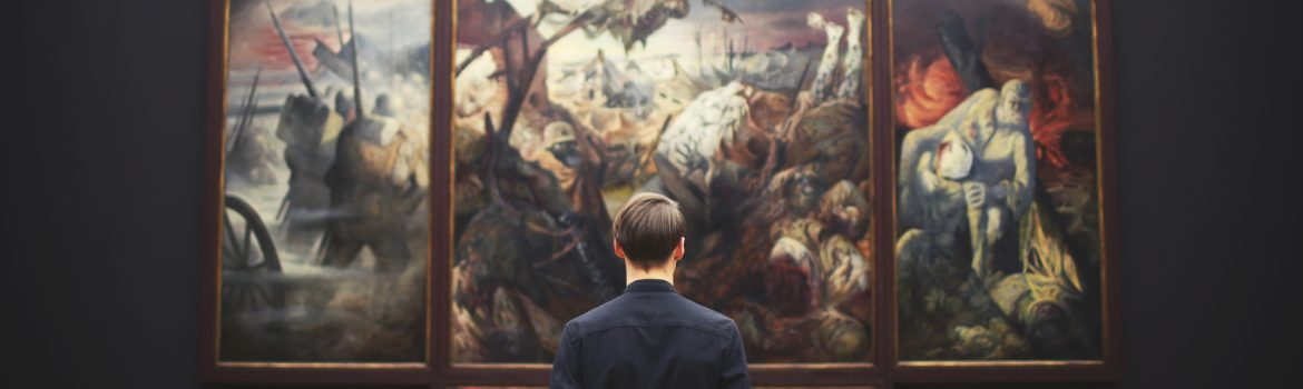 A student in black, in a museum pore over a great painting.