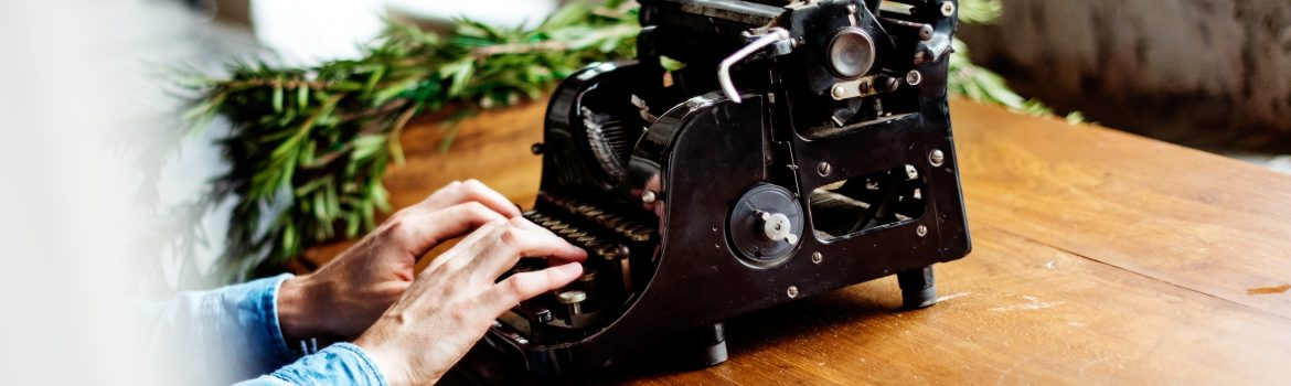 Typing machine and a man typing some text. On the wooden table with green branches.