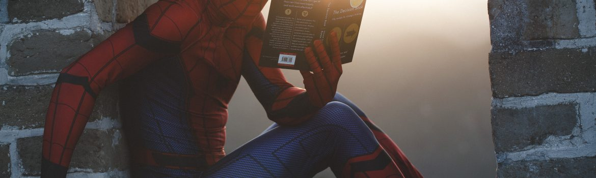 "Spiderman is reading a book about ""Decisions"" sitting on a wall of rocks."