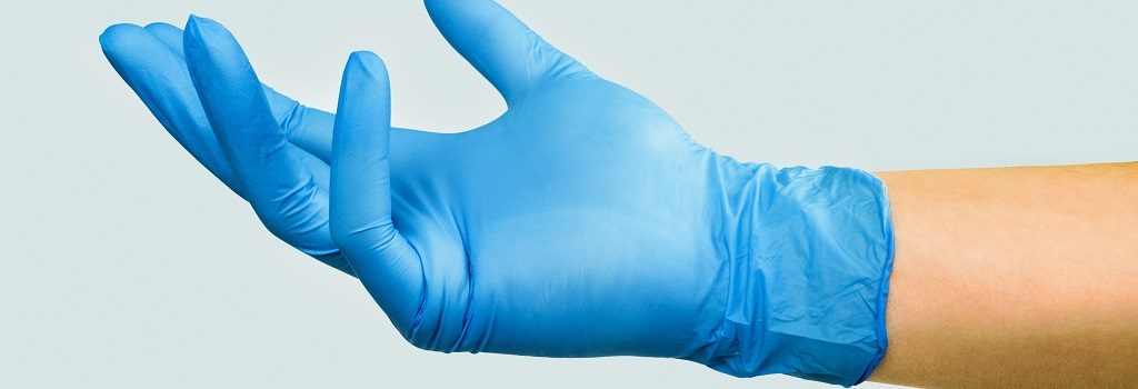 Hand in a blue medical glove