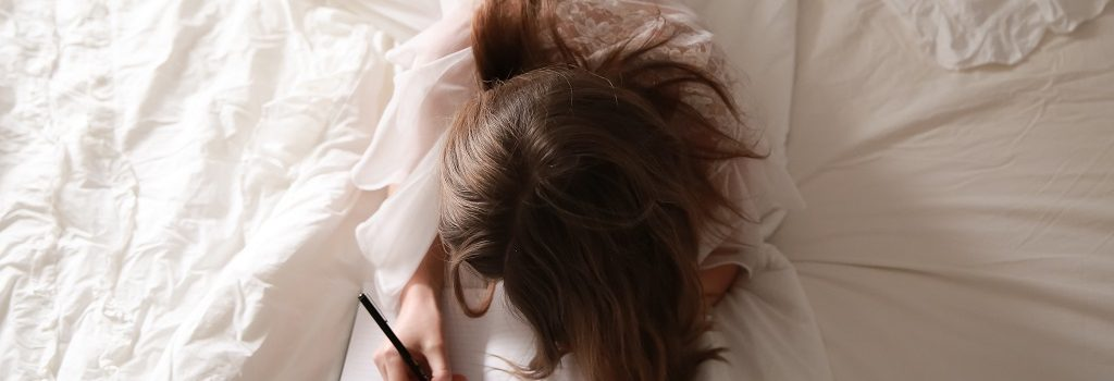 Banner for a post with a girl lying in bed and writing an essay.